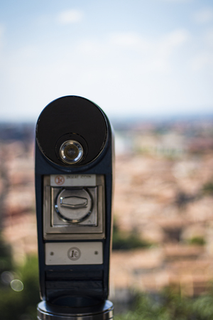 A beautiful image of a telescope against the background of the old city. Back background out of focus
