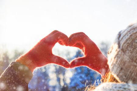 Le mani delle donne in guanto rosso piegate a forma di cuore. Concetto di inverno. Nevicata. Archivio Fotografico