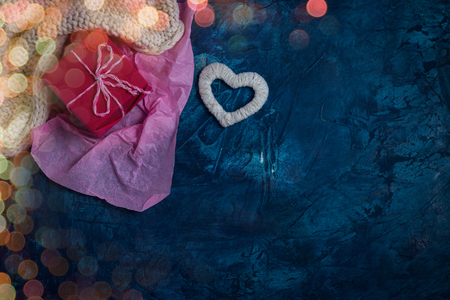 A gift in a pink box on a pink wrapping paper and a white heart on a blue concrete background.