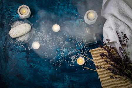 White Towel, Sea Bath Salt, Candles, Handmade Soap on a Dark Dark Blue Background. Added Steam.