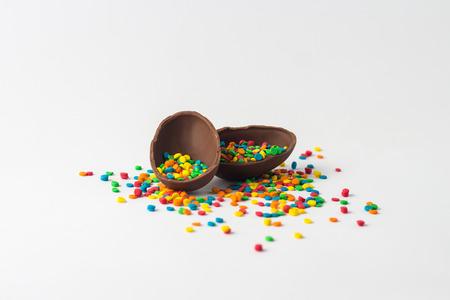 Broken Chocolate Easter egg into two halves with a colorful candy decorations on a white background. Easter concept. Stock Photo