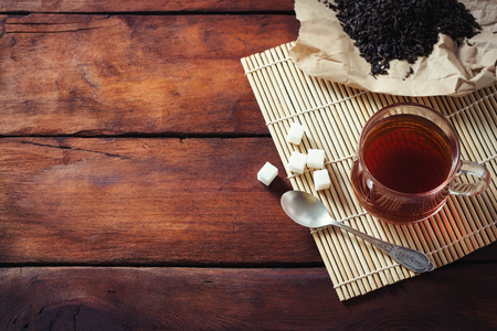 Cup with Tea, Dried Tea Leaves on Kraft Paper, Sugars of Sugar and Spoon on a Wooden Table.