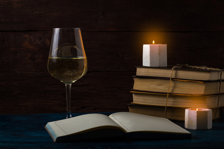 A glass of white wine, an open diary, candles, a stack of books. Romantic Concept.