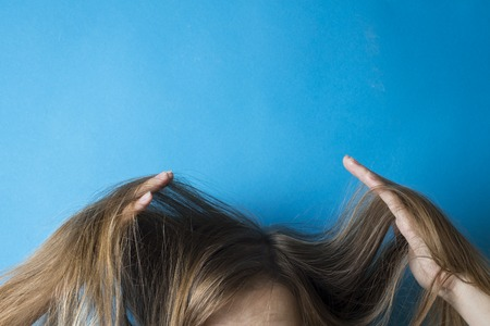 Girl straightens her hair in her hands on a blue background. Preparing for a hairstyle. Modern style. Stock Photo