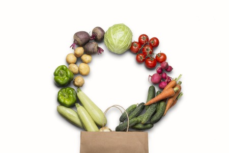 Paper shopping bag and fresh organic vegetables on a white background. Concept of buying farm vegetables, care of health. Circle shape. Country style, Farm Fair. Flat lay, top view.