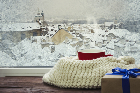 A frozen window and a red cup with hot coffee, a gift and a white scarf, on a pod with a beautiful view of Prague's winter. Banque d'images