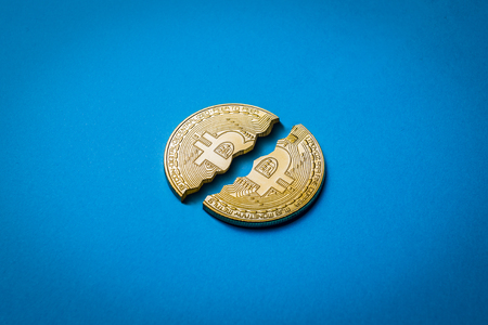 Concept decline and fall cryptocurrency course and a ban on trade. Coin Bitcoin is broken in half on a blue background.