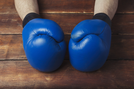 Mens hands in boxing gloves on a wooden background. Ready gesture. The concept of training for boxing training or fighting. Flat lay, top view.