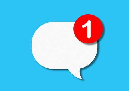White paper cartonboard speech bubble with a red circle with a message about a single message on a blue background. The concept of notification on the phone or social networks. Flat lay, top view.