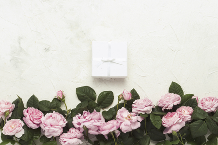 Pink roses, White gift box on a light stone background. flat lay, top view.