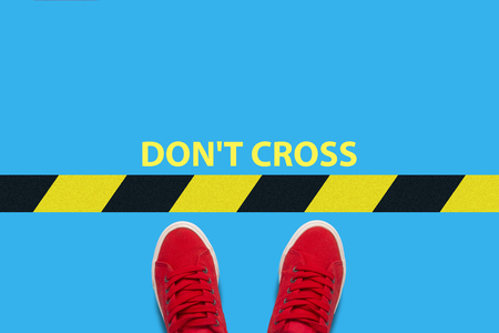 Female feet in red sneakers standing in front of a warning black-and-yellow line with text Don't cross. Concept of the destruction of borders and violations of the rules. Flat lay, top view. 스톡 콘텐츠