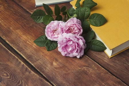Pink roses and book with yellow cover on a wooden background.