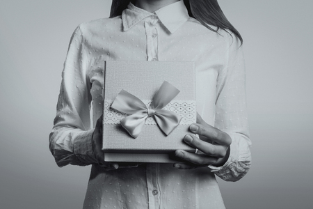 Young girl opens a gift box in front of her. The face of the girl is not visible. Black and white image.