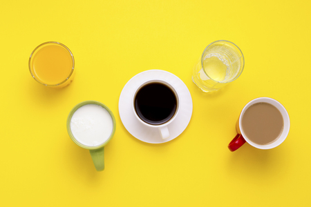 Group of Drinks in Multicolored Cups, Black Coffee, Coffee with Milk, Yogurt, Just Water, Orange Juice on Yellow Background. Flat lay, top view.