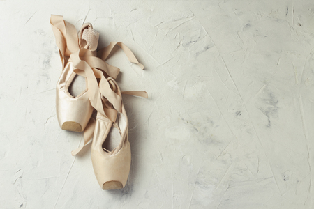 Pointe ballet shoes light stone background. Concept of ballroom dancing.