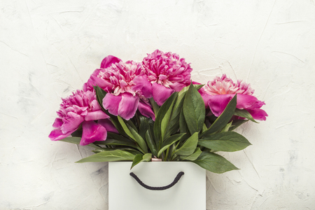Bouquet of peonies in paper bag on white texture Stockfoto