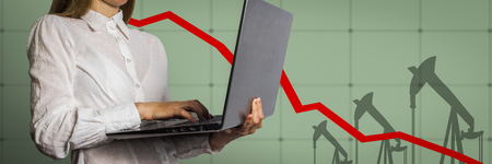 Girl with a laptop in hand and graph chart with the indicator on the oil price slide in the background. The concept of falling oil prices and stock trading.