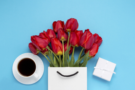 White Gift Bag, a small white gift box, a white cup with black coffee and a bouquet of red tulips on a blue background. Concept Offers an engagement or marriage, shopping.