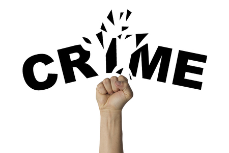Male hand clenched into a fist splits the text CRIME on a white background. Concept of fighting crime. Stock Photo