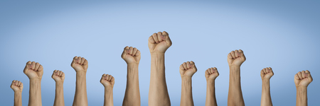 Hands raised up and clenched in a fist on a blue background. Concept of unity of the people, revolution, revolt, riot. Banner.