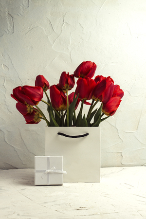 White Gift Bag, small white gift box, petals and bouquet of red tulips on a light stone background. Concept Offer a gift or an engagement, marriage.