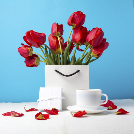 Bouquet of brightly red tulips in a white gift bag, white cup with coffee, white gift box on a blue background. Concept congratulations, surprises and gifts.