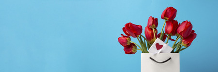 White Gift Bag, a small white gift box with a heart and a bouquet of red tulips on a blue background. Concept Offers an engagement or marriage.