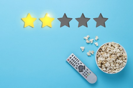 Bowl of popcorn and a remote from the TV set on a blue background. Rating two stars out of five. Concept of the rating of the film, TV series, TV show. Flat lay, top view.