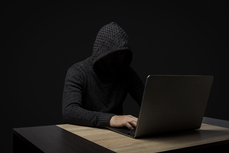 Faceless man in a hooded robe sits at a table with a laptop on a dark background. Concept of hacking and stealing user data. Stock Photo
