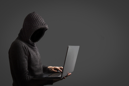 Faceless man in a hoodie with a hood holds a laptop in his hands on dark background. The concept of hacking and stealing user data.