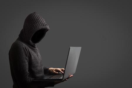 L'uomo senza volto in una felpa con cappuccio tiene in mano un laptop su sfondo scuro. Il concetto di hacking e furto dei dati dell'utente.