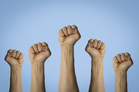 Hands raised up and clenched in a fist on a blue background. Concept of unity of the people, revolution, revolt, riot.