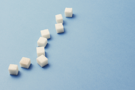 Cubes of sugar on a blue background. The concept of sugar kills and damages the human body. Zdjęcie Seryjne