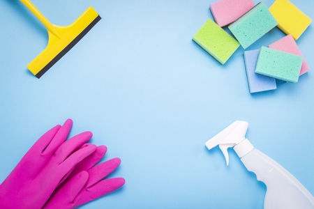 Cleaning and cleaning accessories, Gloves, spray, sponges, scraper for windows on a blue background. Cleaning Service Concept. Copy space. Flat lay, Top view.