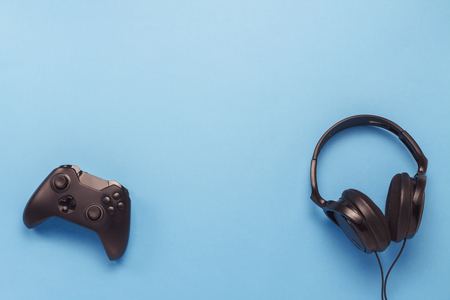 Black headphones and a gamepad on blue background. Concept of the game on the console or computer. Rest after work. Cybersport. Flat lay, top view.
