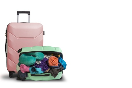 Opened plastic suitcase with wheels, crowded with things and a smaller suitcase standing next to a white background. Travel concept, vacation trip, visit to relatives. Standard-Bild