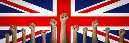 Hands raised up and clenched in a fist against the background of the United Kingdom flag. Concept of unity of the people of Great Britain, revolution, revival, riot. Banner. Reklamní fotografie