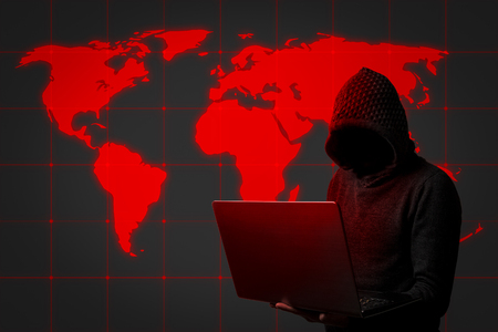 Faceless man in a hoodie with a hood holds a laptop in his hands on dark background. Concept of hacking and stealing user data. Hacked lock, credit card, cloud, email, passwords, personal files.