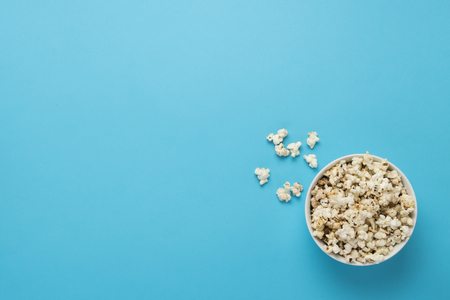 Bowl with popcorn on a blue background. Concept home theater, movie, leisure. Flat lay, top view. Stock Photo