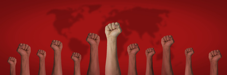 Hands raised up and closed in a fist on a red background with a map of the earth. Concept of unity of the people, revolution, revolt, riot. Banner.
