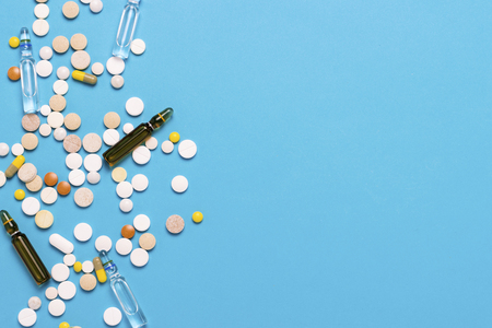 Pills of different colors and ampoules with medicine on a blue background. Concept of the pharmaceutical industry, medicine, treatment and recovery after illness. Flat lay, top view.