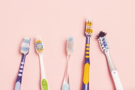 Mehrere verschiedene gebrauchte Zahnbürsten auf rosa Hintergrund. Zahnbürstenwechselkonzept, Mundhygiene, große und freundliche Familie, Zahnbürstenauswahl. Flache Lage, Ansicht von oben Standard-Bild
