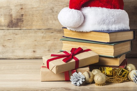 A stack of books, Santa Claus's cap, an alarm clock, cones, Christmas-tree decorations, gift boxes on a wooden background. Concept of New Year and Merry Christmas