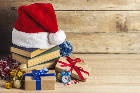 A stack of books, Santa Claus's cap, an alarm clock, gift boxes on a wooden background. Concept of New Year and Merry Christmas