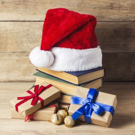 A stack of books, Santa Claus's cap, gift boxes with red and blue ribbons on a wooden background. Concept of New Year and Merry Christmas