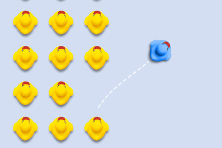 Group of yellow ducklings moves in line direction, but one blue duck swims in another direction. Blue background. The concept of innovative and creative business solutions. Flat lay, top view