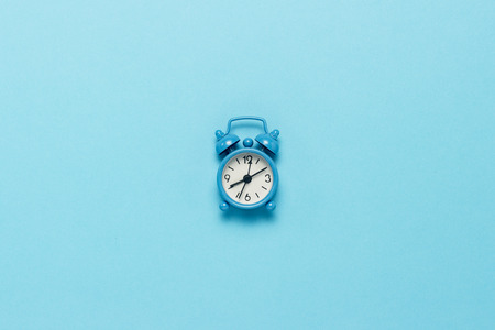 Blue alarm clock on a blue background. Concept day and night, time management, planning, schedule of day and night, minimalism. Flat lay, top view