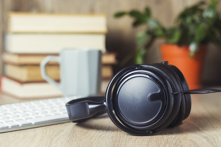 Headphones, keyboard, stack of books and cup on the office desk. Office concept, work day, hourly pay, work schedule, work in a call center