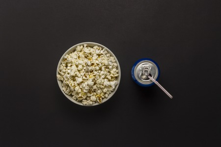 Bowl with popcorn and a can of drink on a black background. The concept of watching movies and favorite TV shows, sports competitions. Flat lay, top view 스톡 콘텐츠