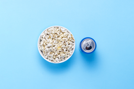 Bowl with popcorn and a can of drink on a blue background. The concept of watching movies and favorite TV shows, sports competitions. Flat lay, top view 스톡 콘텐츠